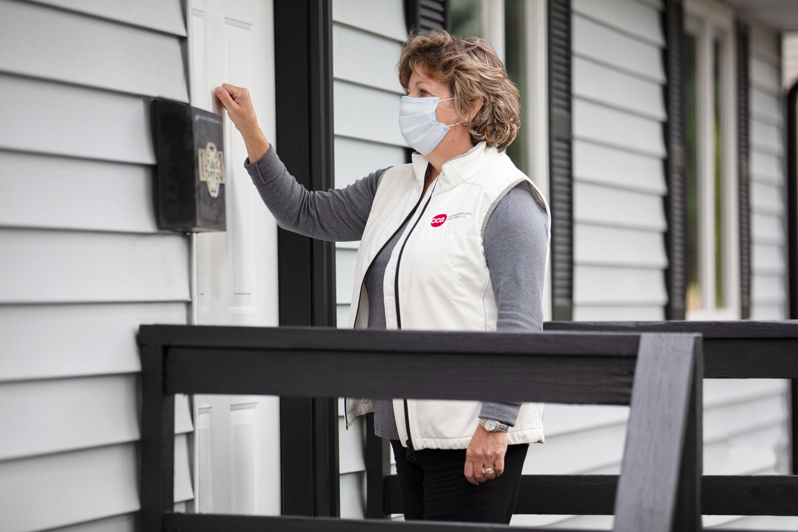 Female care provider with mask wearing CCA vest knocking on a member's front door