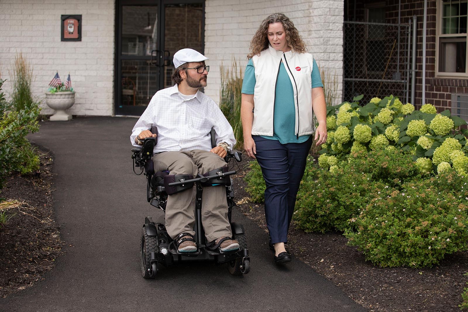 Disabled man in wheelchair and female care partner talking outdoors on walkway