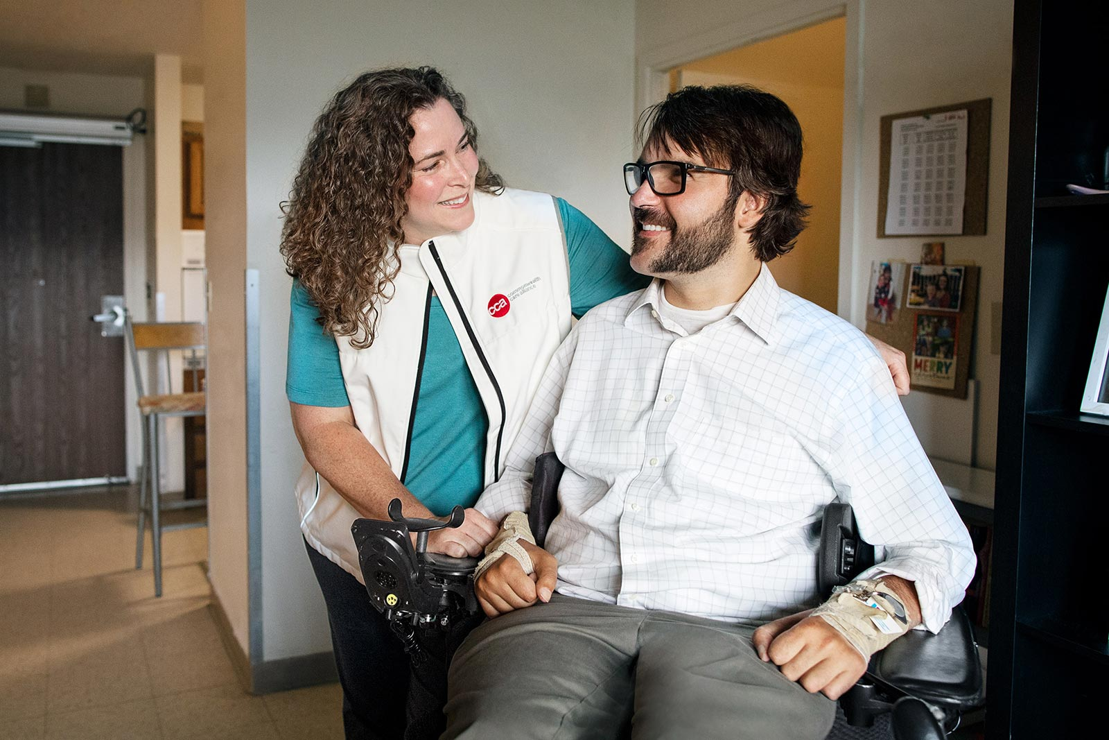 Disabled man in wheelchair smiling in his home with female care partner