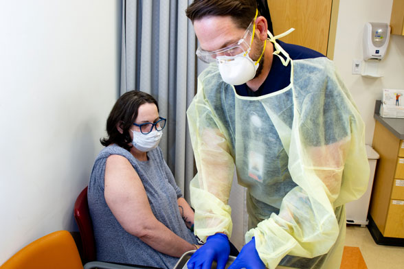 Male nurse in glove, mask, goggles, and gown preparing vaccine in doctor's office for sitting female patient