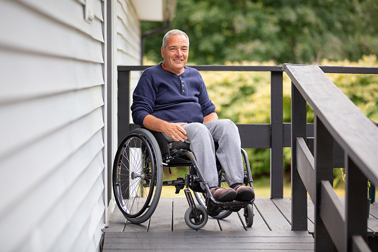 One Care member in wheelchair and blue shirt smiling outdoors on his home porch