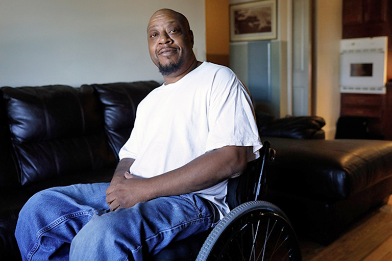 CCA member seated in wheelchair in his living room
