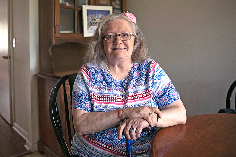 Older woman with arms crossed over her cane smiling at home in her dining room