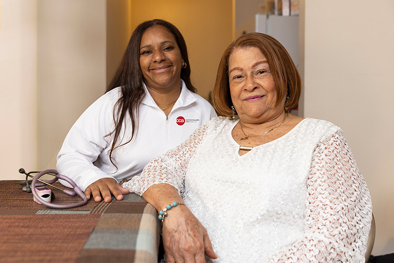 Senior woman sitting with her CCA care partner in her home