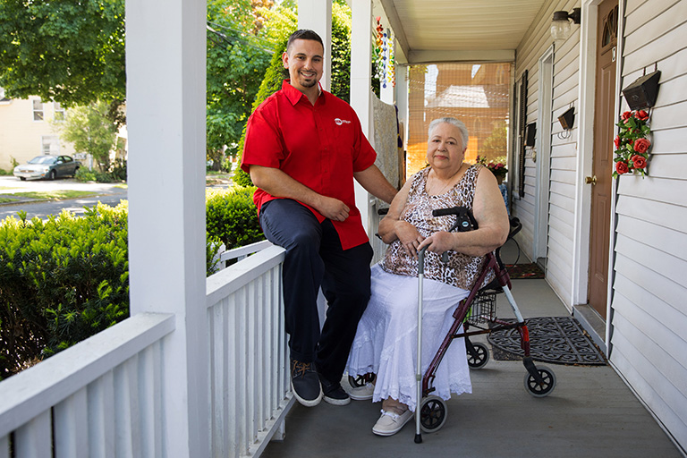 CCA SCO member seated in walker on her porch next to her care partner