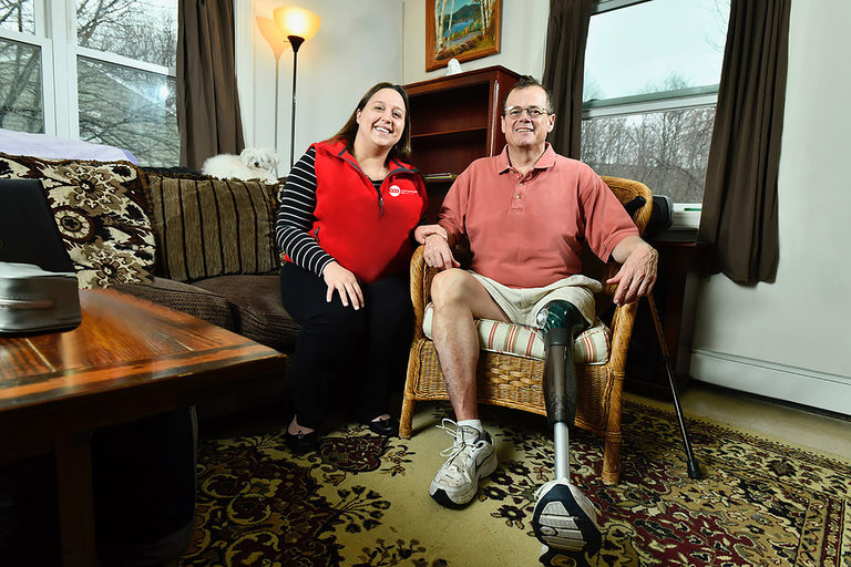 CCA One Care member Mike showing his prosthetic leg while seated in living room with his care partner