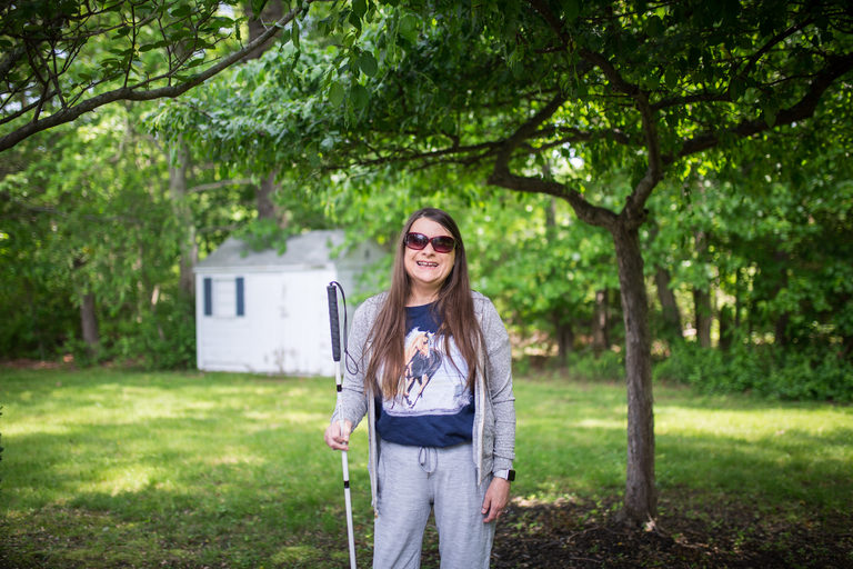 One Care member Marie standing and smiling outside with sunglasses and white cane