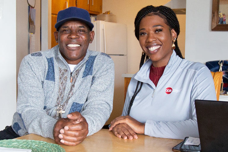 Female care provider sitting and smiling at kitchen table with middle-aged male member