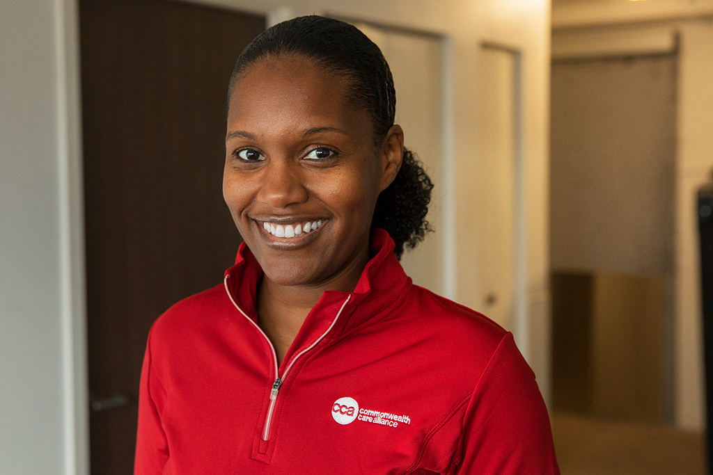 Smiling young female care provider wearing Commonwealth Care Alliance jacket
