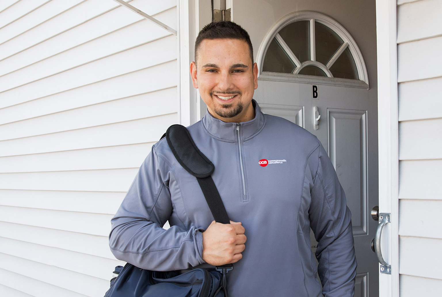 Young male professional standing in front of his home with professional bag over shoulder wearing CCA jacket