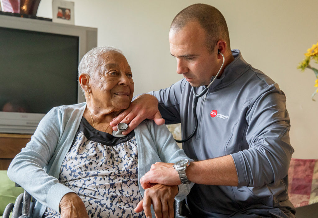 Elderly female patient receiving home care from male medical professional
