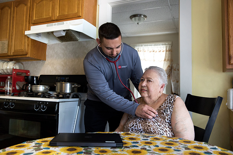 CCA SCO member sits at kitchen table while care partner listens to her heart