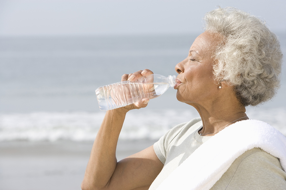 A Black senior woman drinking water from bottle with sea in the background