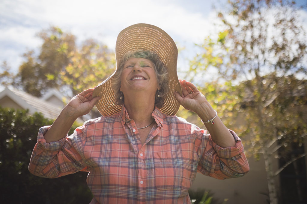 Senior woman wearing a large brimmed hat in the sun