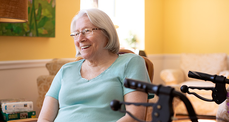 Happy woman with walker in her living room